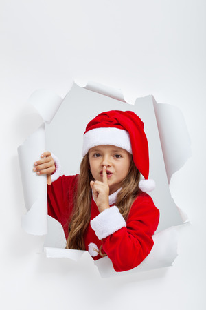 jagged: Little girl in christmas outfit telling you a secret - leaning out of a jagged edge hole