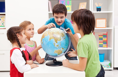 Kids working on a science project - using an earth globe to search for locations photo