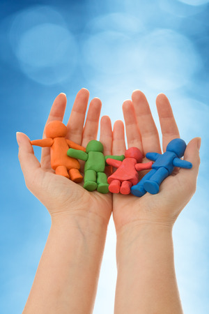 caring hands: Colorful clay people in woman palm - agains blurred blue background
