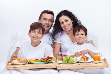 ni�os desayuno: Familia feliz que desayuna en la cama en una ma�ana brillante