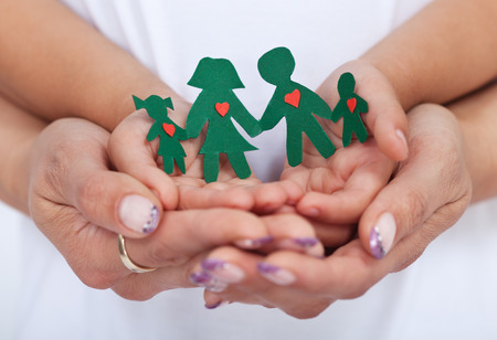 Loving family concept with adult and child hands holding paper people- shallow depth of field photo
