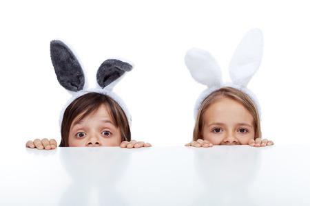 oreja: Los ni�os con orejas de conejo miran a escondidas de debajo de la mesa - esperando el Conejo de Pascua Foto de archivo