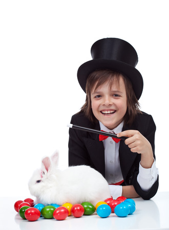 conjuring: The magic of easter - happy magician boy conjuring a grumpy rabbit and colorful eggs, isolated