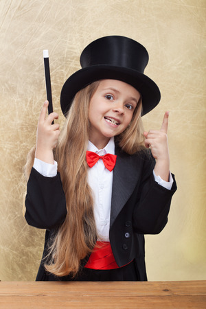 Funny magician girl with magic wand and hat - on golden background