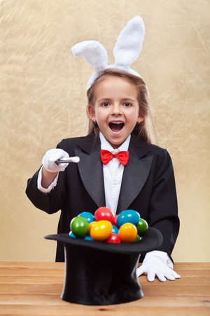 conjuring: Happy magician girl with bunny ears conjuring colorful easter eggs