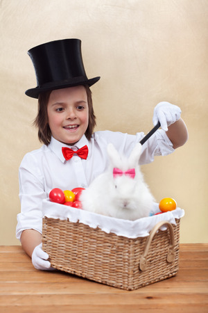 conjuring: Happy magician boy conjuring an easter rabbit and colorful eggs into a basket Stock Photo