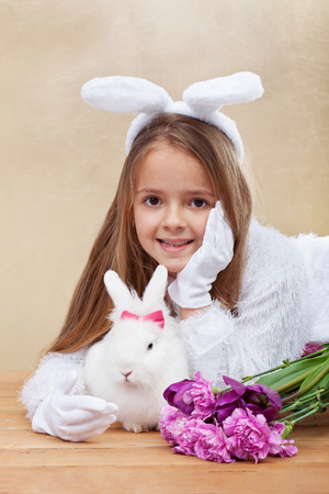 frienship: Cute bunnies with spring flowers - little girl with bunny ears and white rabbit