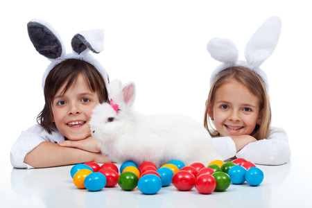 white rabbit: Happy kids at easter time - wearing bunny ears and guarding their white rabbit and colorful eggs