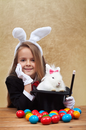 conjuring: Young magician after successfully conjuring an easter rabbit - sitting with satisfaction