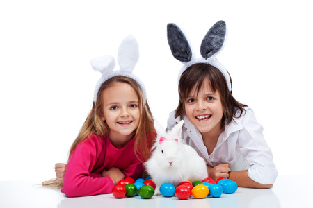 Happy kids with the easter bunny and colorful eggs - wearing bunny ears photo