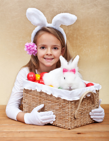 Happy spring girl with easter basket - holding colorful eggs and white rabbit photo