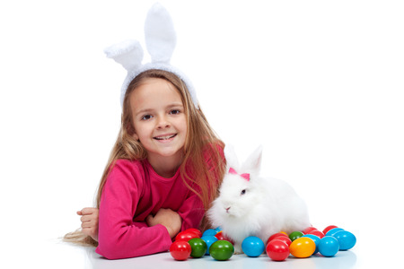 Happy girl with her easter rabbit and colorful dyed eggs - isolated photo
