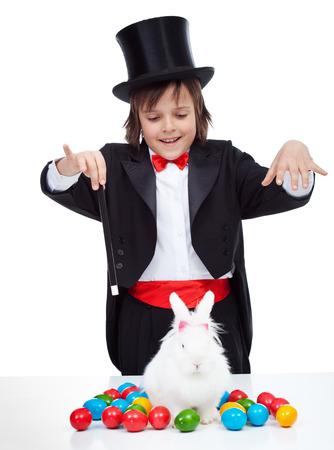 mago: Niño mago joven que realiza un truco de Pascua - conjurando un conejo blanco con huevos de colores, aislados