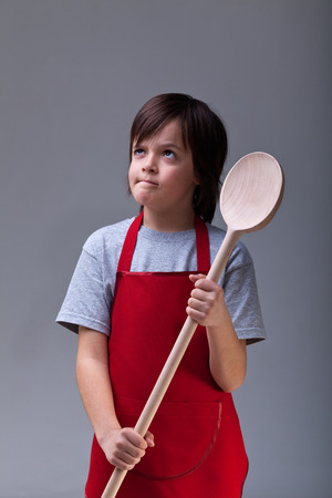 oversized: What should I cook today - young chef boy with large wooden spoon Stock Photo