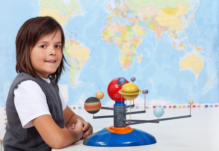 human geography: Young boy in school learning about the solar system Stock Photo