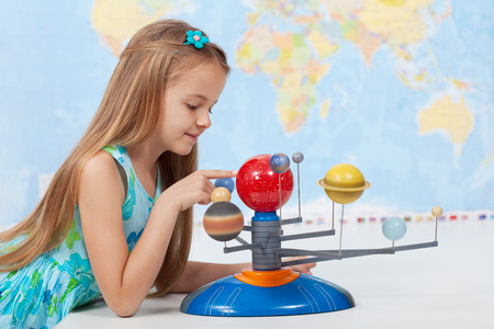 solar system: Little girl studies the solar system in geography class - looking at the scale model of planets