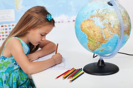 geography: Little girl coloring the world map in elementary school geography class Stock Photo