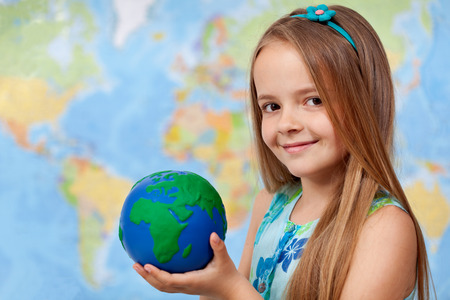The world in my hands - little girl in geography class holding earth globe, copy space