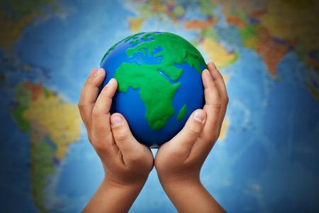 Ecologie concept met earth globe in kind handen tegen onscherpe wereldkaart
