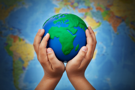 peace symbols: Ecology concept with earth globe in child hands against blurry world map