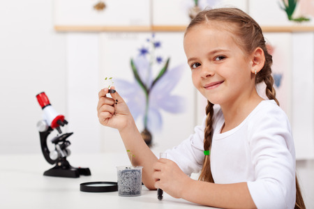 Young girl study plants in biology class  holding a seedling and test tube