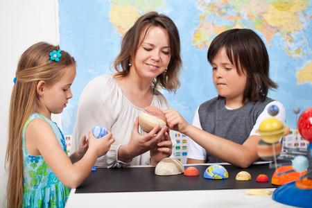 maestro: Niños y profesor en clase de ciencias estudian el sistema solar examinar los planetas a partir de un modelo a escala Foto de archivo