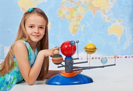 happy planet earth: Sistema Solar estudio de la chica joven en la clase de ciencias geograf�a utilizando un modelo a escala Foto de archivo