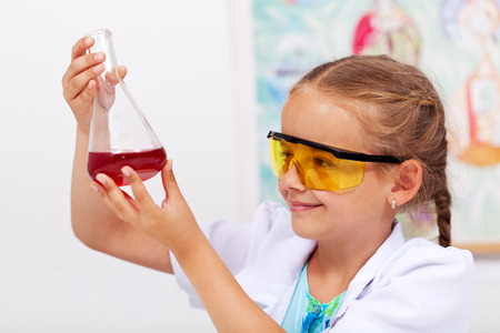 recipient: Young student in chemistry class looking at glass recipient