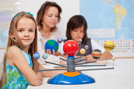 system: Kids study the solar system under their teacher supervision - focus on the little girl in front