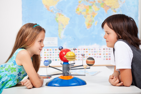 solar system: Kids with a scale model planetary system in geography science class discussing Stock Photo