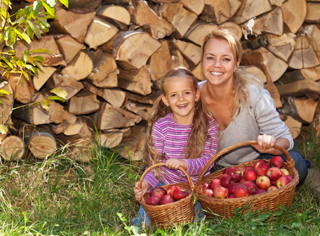 harvesters: Happy harvesters in autumn - laughing child and woman with red apples in baskets