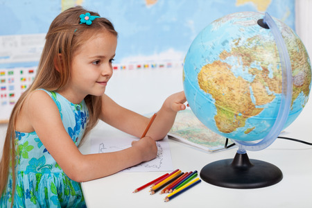 educational subject: Young girl in geography class learning about our planet