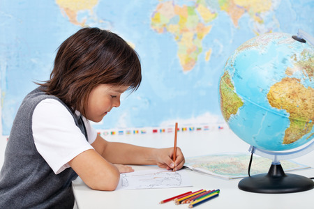 human geography: Young boy study geography in science class - coloring a world map