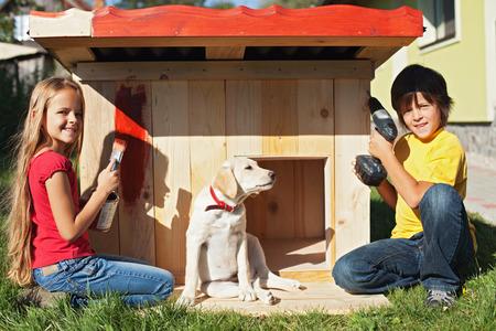 새로운 강아지를위한 쉼터를 준비하는 아이들은 - 마무리 및 개집 그림 스톡 콘텐츠