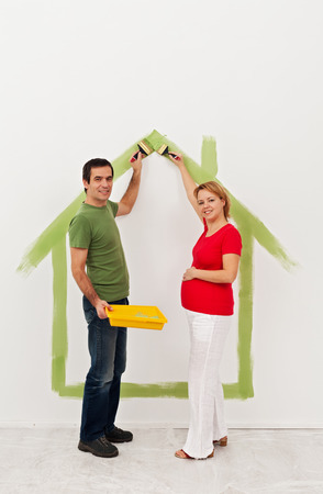 Young couple expecting a baby - preparing the child room in their new home photo