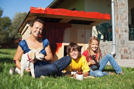 perrito: Familia preparar la caseta del perro para el nuevo miembro de la familia - un cachorro de labrador
