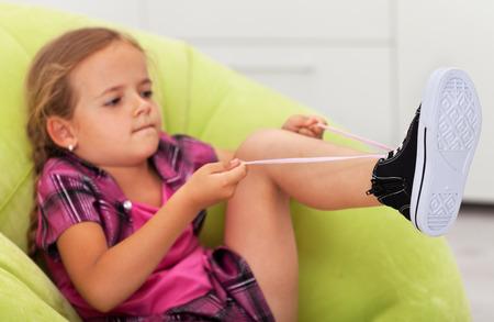 manos y pies: La lucha - ni�a linda concentr� para atar el zapato, se centran en los pies
