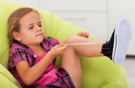 cute little girl: The struggle - cute little girl concentrated to tie shoe, focus on the feet
