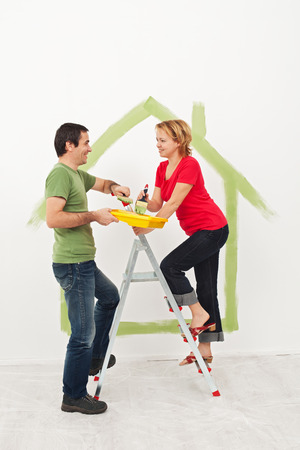 Young couple  creating their new home - drawing the conceptual blueprints photo