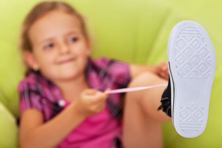 teen feet: Little girl struggling to tie her shoes - focus on foot, copy space