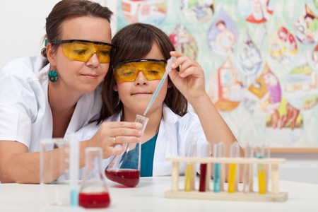 Young boy in elementary science class doing chemical experiment helped by teacher Stockfoto