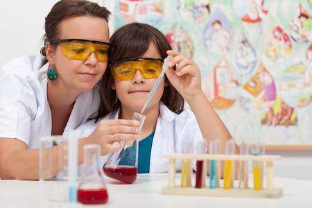 experimento: Muchacho joven en la clase de ciencias de primaria haciendo experimento químico ayudado por el maestro