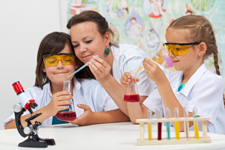 Chemical experiments in elementary school - kids helped by teacher in science class