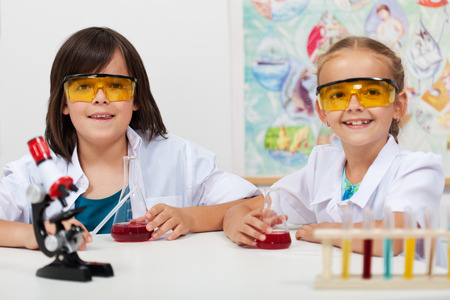 young students: Kids in elementary science class doing chemical experiments Stock Photo