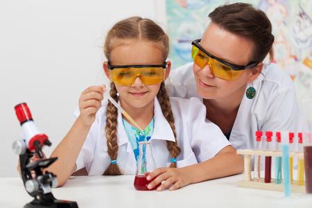 experimento: Profesor experimento químico supervisión en la clase de ciencias de la escuela primaria