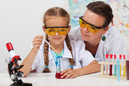 overseeing: Teacher overseeing chemical experiment in elementary school science class