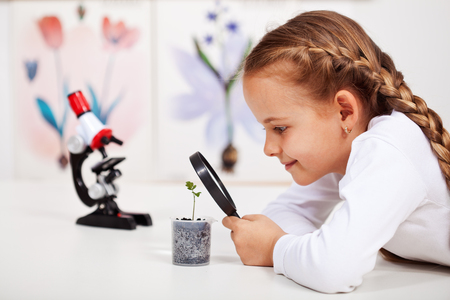 microscopio: Joven estudiante estudia pequeña planta en la clase de ciencias de primaria