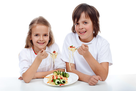 family isolated: Happy kids eating a pasta dish - isolated Stock Photo