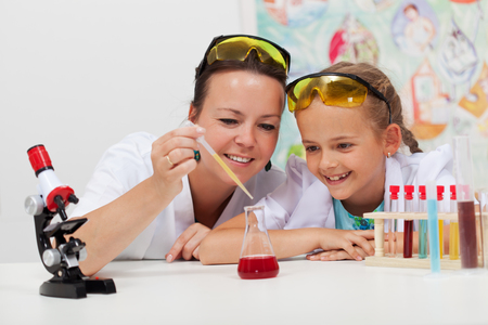 interesting: Young student and teacher in elementary science class doing a chemical experiment
