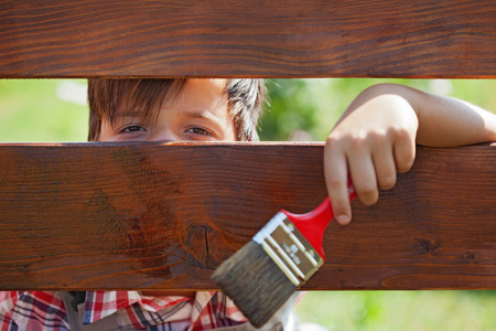 prying: Young boy painting the wooden fence - peeking through the planks Stock Photo